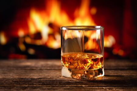 Whiskey in a glass with fire in the fireplace on the background Imagens