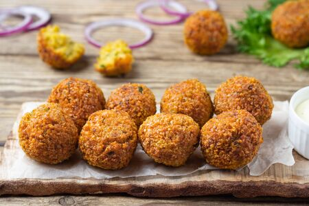 Vegetarian dish - falafel balls from spiced chickpeas on wooden rustic table. 版權商用圖片