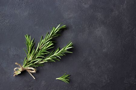 Rosemary herbs on dark stone background. Top view. Copy space.
