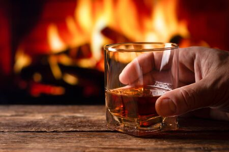 A glass of whiskey in a man hand. Blur burning fireplace background. Imagens