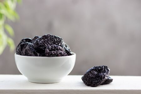 Dried prunes in a bowl on white table