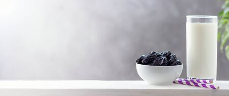 Concept healthy food, vegetarianism, diet. A glass of yogurt and prunes. Bright background with copy space.