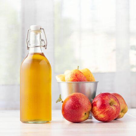 Gesundes Bio-Lebensmittel. Apfelessig oder Saft in Glasflasche und frische rote Äpfel auf hellem Hintergrund. Standard-Bild