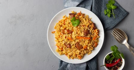 Traditional asian dish - pilaf from from rice, vegetables and meat in a plate on gray background. Top view with copy space.