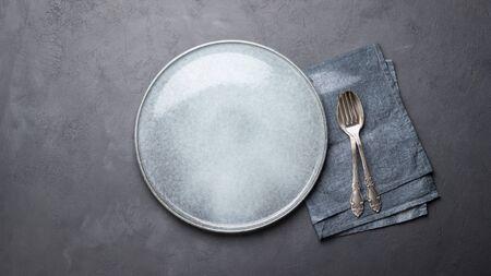 Lunch- of dinerconcept. Tafel opstelling. Bord, bestek en servet over grijze betonnen achtergrond.