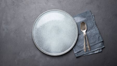 Lunch or dinner concept. Table setting. Plate, cutlery and napkin over gray concrete background.