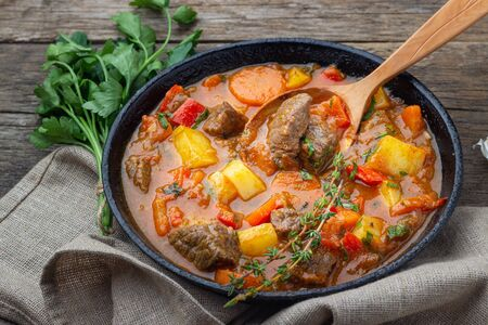 Goulash, beef stew or bogrash soup with meat, vegetables and spices in cast iron pan on wooden table. Hungarian cuisine. Rustic style. 版權商用圖片