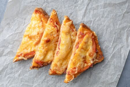 Sandwiches cooked in the oven with tomato and cheese on a paper. View from above.