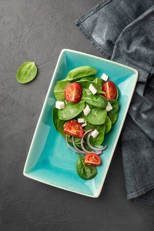 Above view of a fresh green vegetable salad of spinach, tomato and sesame seeds on a blue rectangular plate. Black background. Copy space for text. 版權商用圖片
