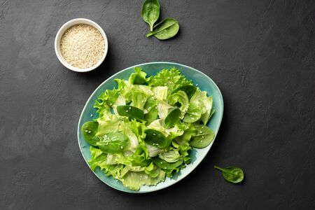 Healthy food. Top view of a fresh green vegetable salad of spinach, lettuce and sesame seeds on a plate. Black background.