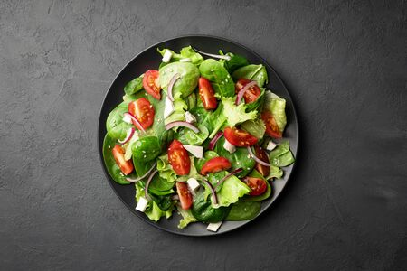 Healthy food. Top view of a fresh green vegetable salad of spinach, tomato, lettuce and sesame seeds on a plate. Black background.