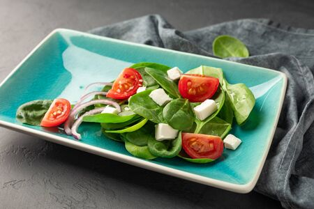 Fresh green vegetable salad of spinach, tomato and sesame seeds on a blue rectangular plate. Dark background.