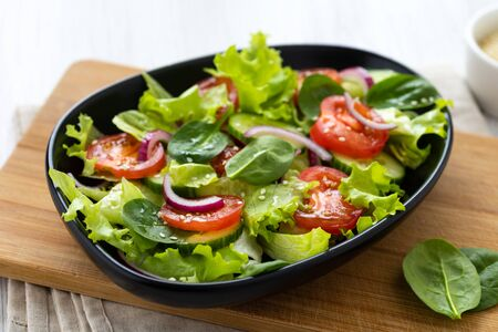 Healthy vegetable salad from fresh vegetables of tomato, spinach, cucumber, lettuce and sesame on a plate. Useful nutrition.