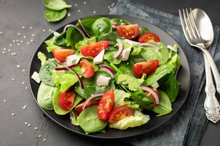 Healthy vegetable salad from fresh vegetables of tomato, spinach, lettuce and sesame on a plate. Useful nutrition. 版權商用圖片