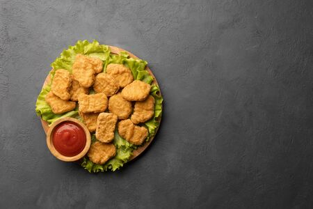 Fried crispy chicken nuggets with ketchup. Top view with copy space. Black background.