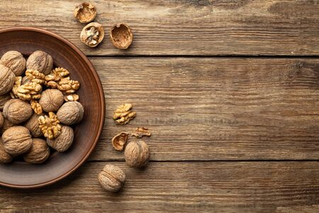 Nuts. Walnut kernels and whole walnuts on a table. Wooden background. Top view, flat lay with copy space.
