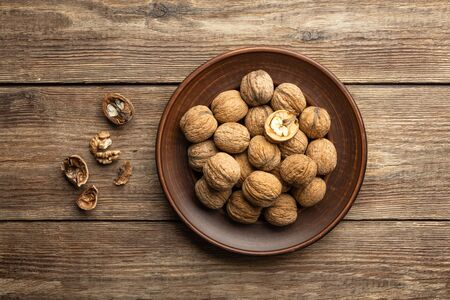 Nuts. Walnut kernels and whole walnuts on a table. Wooden background. Top view, flat lay.