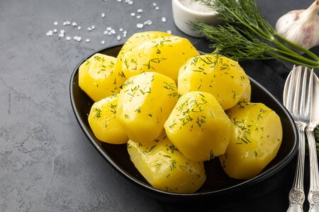 Delicious boiled potatoes with dill in a black plate. 版權商用圖片