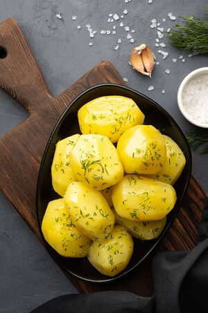 Delicious boiled potatoes with dill in a black plate. Top view, flat lay. 版權商用圖片