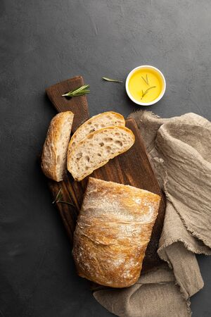 Crispy italian ciabatta bread on black background. Top view, flat lay.