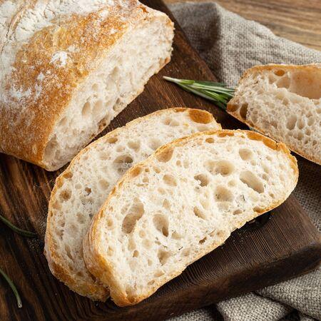 Delicious homemade sliced Italian ciabatta bread on a wooden cutting board. Close-up.