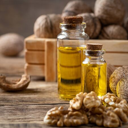 Glass bottle with walnut oil and walnut kernel on a wooden table. Cosmetic and therapeutic product.