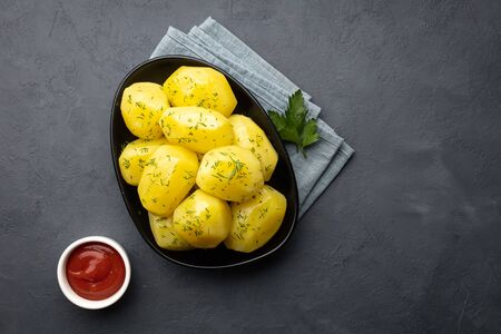 Delicious boiled potatoes with dill and ketchup on a black background. Top view, flat lay.