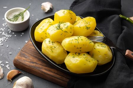 Boiled potatoes with dill and oil on plate