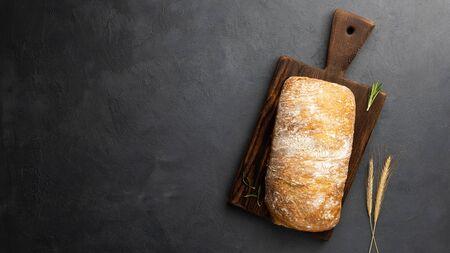 Crispy Italian ciabatta bread on black background. Top view, flat lay. Copy space for text. 版權商用圖片