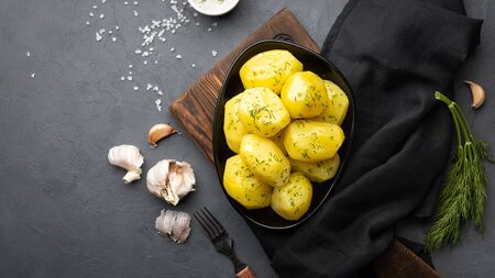 Boiled potatoes with dill and oil on black background. Top view, flat lay.