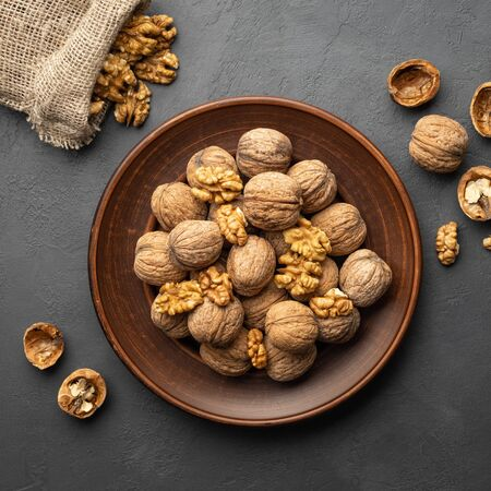 Nuts. Walnut kernels and whole walnuts on dark stone table. Top view, flat lay.