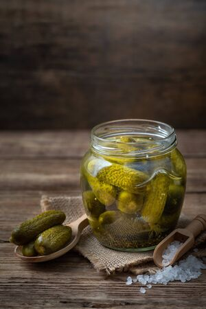 Pickled cucumbers in a glass jar on a wooden table. 版權商用圖片