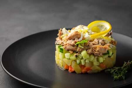 Salad with canned tuna and vegetables in culinary ring on black plate. Dark background. Beautiful serving in the restaurant. 版權商用圖片