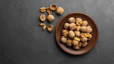 Nuts. Walnut kernels and whole walnuts on dark stone table. Black background. Top view, flat lay with copy space. 版權商用圖片