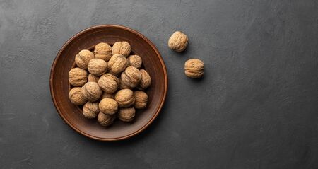 Whole walnuts on black stone background. Above view, flat lay. Copy space for text. 版權商用圖片