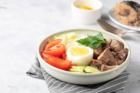 Salad with canned tuna, egg and vegetables - tomatoes, cucumber and lettuce.
