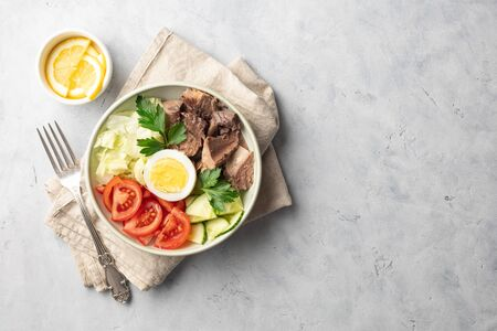 Salad with canned tuna, egg and vegetables - tomatoes, cucumber and lettuce. Top view. Light background. Copy space for text. 版權商用圖片