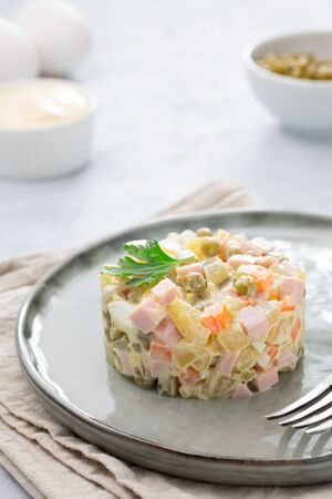 Russian salad Olivier with mayonnaise and egg served in culinary ring on plate. Light background. 版權商用圖片