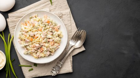 Russian salad Olivier with eggs and mayonnaise on plate. Top view. Black background. Copy space. 版權商用圖片