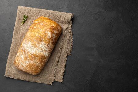 Sliced Italian ciabatta bread on dark background. Above view. Copy space for text. 版權商用圖片