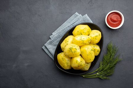 Boiled potatoes with herbs in rustic bowl on wooden cutting board with silverware, salt, garlic and fresh herbs on slate with copy space.