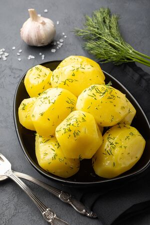 Boiled potatoes with herbs in rustic bowl with silverware, salt, garlic and fresh herbs on slate.