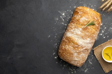 Sliced Italian ciabatta bread on black background. Top view, flat lay. Copy space for text. 版權商用圖片
