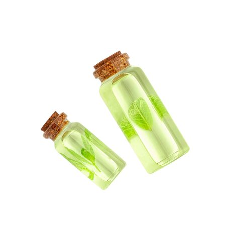 Glass transparent bottles with essential oil and mint isolated on white background. Top view.
