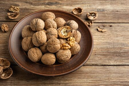 Nuts. Walnut kernels and whole walnuts on wooden table.
