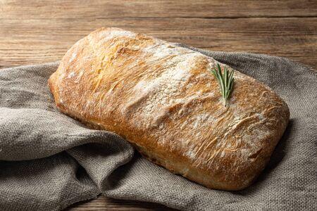 Crispy italian ciabatta bread on burlap on wooden table.
