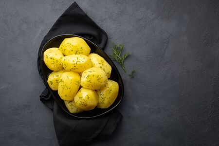 Delicious boiled potatoes with dill in a black plate on a dark background. Top view.