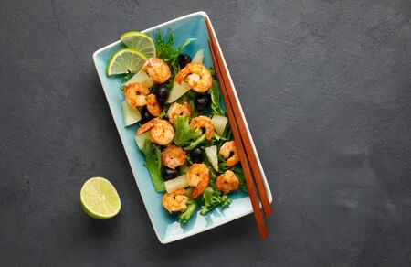 Salad with shrimp, pineapple and fresh herbs in a blue plate on a black background. Healthy food. Top view. Stock Photo