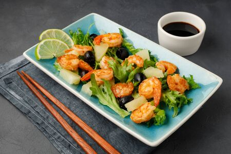 Salad with shrimp, pineapple and fresh herbs in a blue plate on a black background. Healthy food.