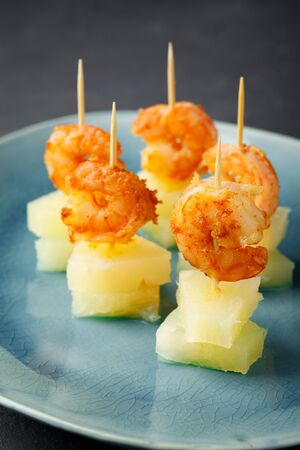 Canapes with shrimp and pineapple. Party food. Dark background. Imagens